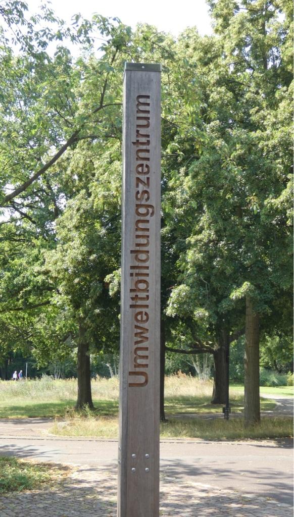 Ein Hinweisschild mit dem Schriftzug Umweltbildungszemtrum vor geünbelaubten Bäumen